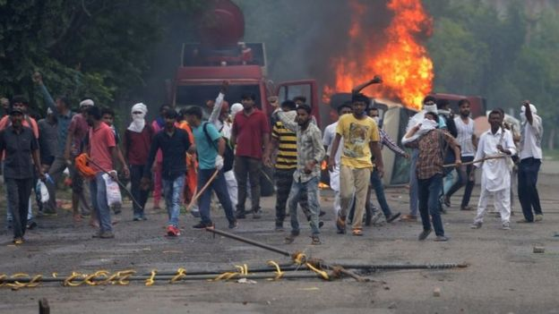 Supporters of Indian religious leader Gurmeet Ram Rahim Singh throw stones at security forces next to burning vehicles during clashes in Panchkula on August 25, 2017.