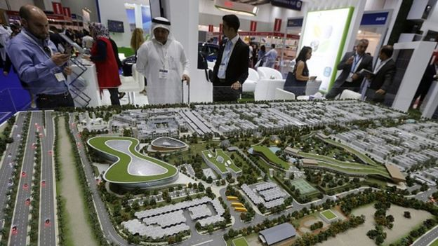Visitors gather near a model of a solar city during the 'Inter Solar Connecting Solar Business' exhibition in Dubai (19 September 2016)