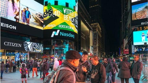 Imagen nocturna de gente caminando por la ciudad de Nueva York. Zona de Times Square