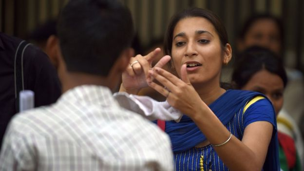 Indian deaf activists interact with sign language during a protest in New Delhi on May 5, 2015