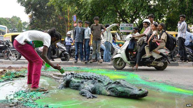 Indian artist creates crocodile pothole to get road fixed