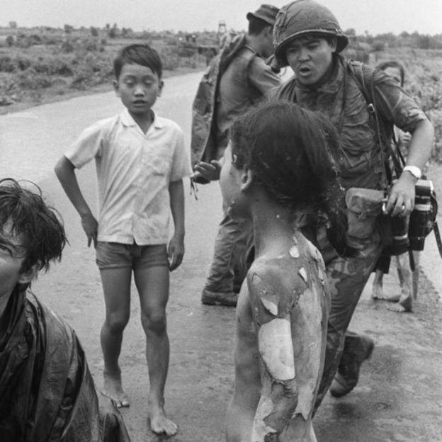 Niños tras el ataque de napalm en 1972 sobre la aldea de Trang Bang. Se ve a Nick Ut con sus cámaras colgando y a Kim desnuda de espalda con la piel que cae como en gajos