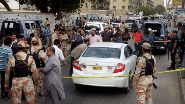 Pakistani investigators and journalists gather around the blood-stained car of famous Sufi singer Amjad Sabri after an attack in Karachi, Pakistan, Wednesday, June 22, 2016.