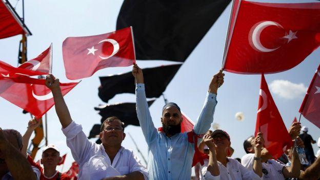 Miting alanında ellerinde Türk bayrağı olan kalabalık