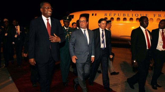 French President Francois Hollande (C) is received by Nigerian Foreign Minister Geoffrey Onyeama (L) on arrival in Abuja, Nigeria, 13 May