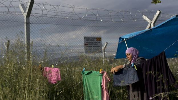 Woman hangs laundry near Greece-Macedonia border fence - 15 May
