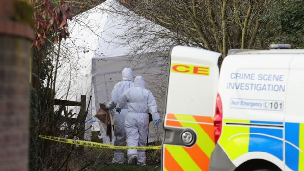Forensic officers walking to a white tent