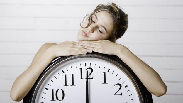 Mujer reposando sobre un reloj.