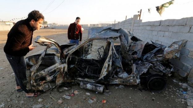 Men look at the wreckage of a burnt car after a suicide bomber detonated a pick-up truck in Sadr City on Wednesday (15 February 2017)
