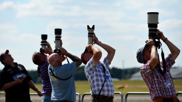 Aircraft enthusiasts photograph an air display at the Farnborough air show