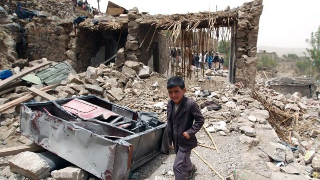 A Yemeni boy walks past the rubble of destroyed houses in the village of Bani Matar, about 70km west of Sanaa, on 4 April 2015,