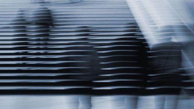 Imágenes desdibujadas de personas que suben por unas escaleras.