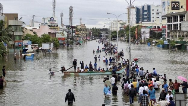 People travel on a boat as they move to safer places through a flooded road in Chennai, India, December 2, 2015.