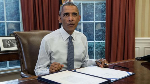 US President Barack Obama prepares to sign a $1 trillion stopgap spending bill in the Oval Office of the White House in Washington, DC, on September 19, 2014.