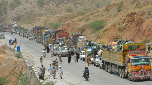 A line of vehicles are pictured as Pakistani civilians, fleeing a military operation in North Waziristan, wait to cross a checkpoint at the Bannu Frontier Region registration centre for internally displaced people in Saidgai on 22 June 2014