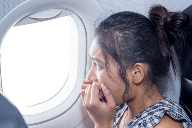 Mujer con cara de miedo en un avión