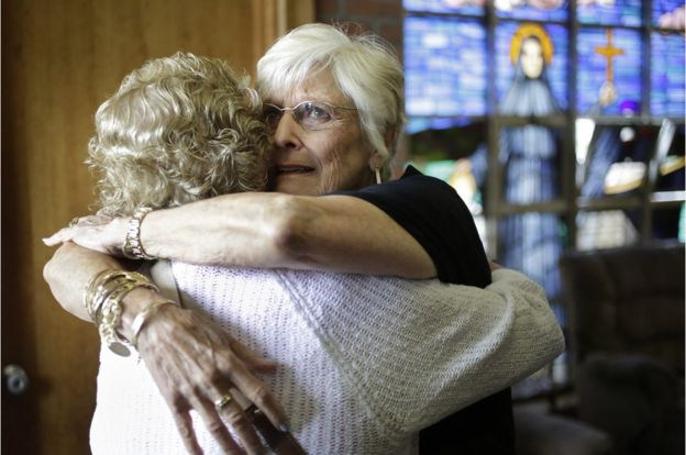 Nancy Shilts hugs another parishioner before the final service
