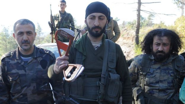Alpaslan Celik, a deputy commander in a Syrian Turkmen rebel brigade, holds handles believed to be parts of a parachute of the downed Russian warplane (24 November 2015)