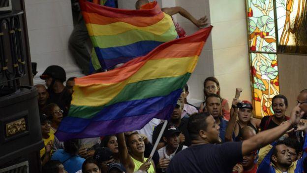 Grupos de manifestantes con banderas arcoiris
