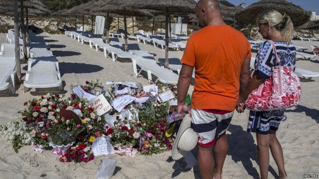 Tourists holding hands looking at tributes on beach