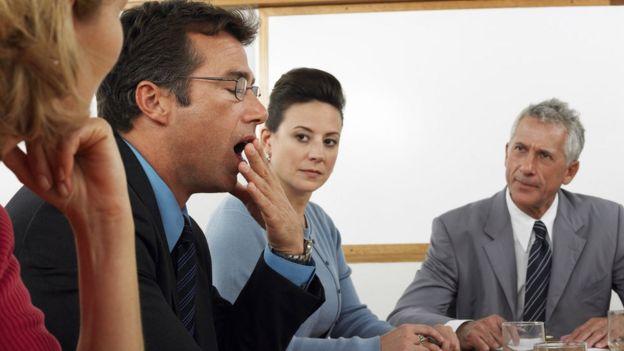 Un hombre bostezando en una reunión.