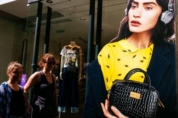 Mulheres passam em frente a uma vitrine em Paris