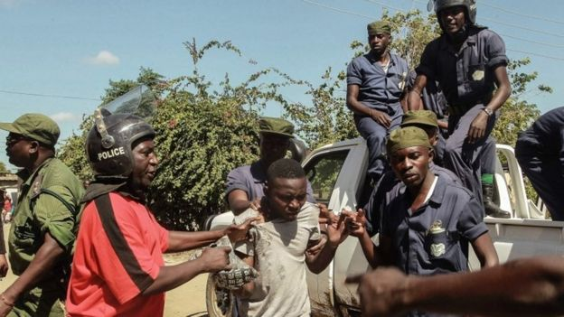Zambian Police apprehend an alleged looter in the Zingalume Compound where residents have attacked broken and looted foreign-run shops in Lusaka on April 19, 2016