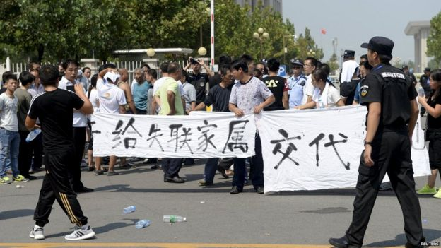 Relatives unfurl a banner during a protest to demand information about their relatives' whereabouts at Tianjin on 16 August 2015