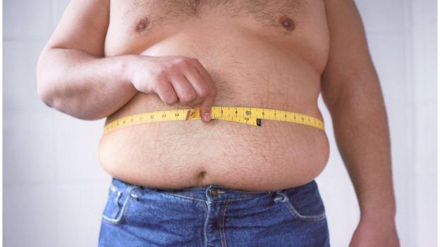 Hombre midiéndose la barriga
