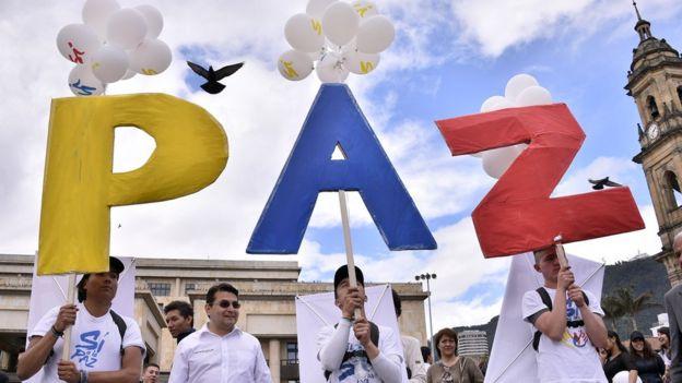 Manifestantes sostienen un cartel con la palabra Paz en Bogotá, Colombia.