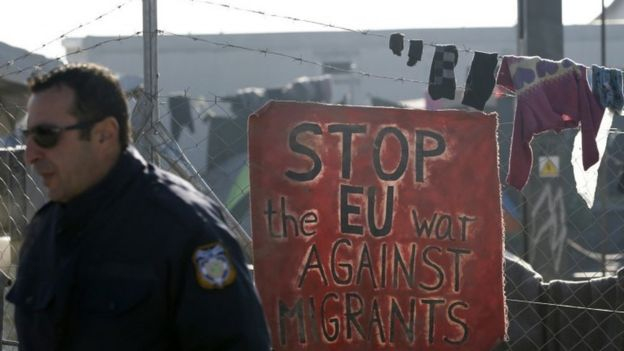 A Greek police officer passes by a banner in the makeshift refugee camp at the northern Greek border point of Idomeni, Greece