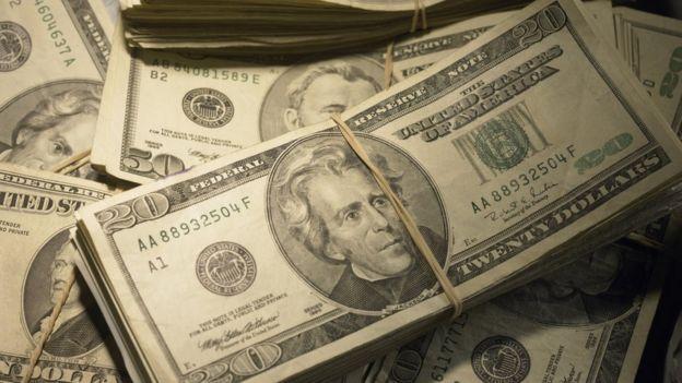 Fajos de billetes de dólares acumulados unos sobre otros.