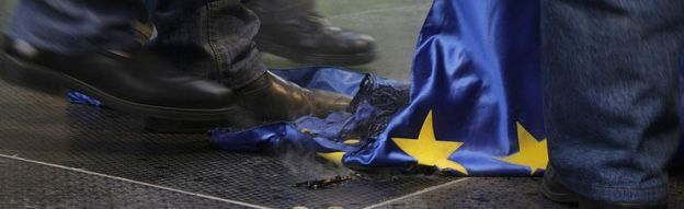 Protesters trample a burnt European Union flag during a demonstration untitled 'To be members, or to be free?' and called by the right-wing parliamentary party 'Jobbik' against European Union in front of the European Union Parliament and Committee headquarters in downtown Budapest on January 14, 2012
