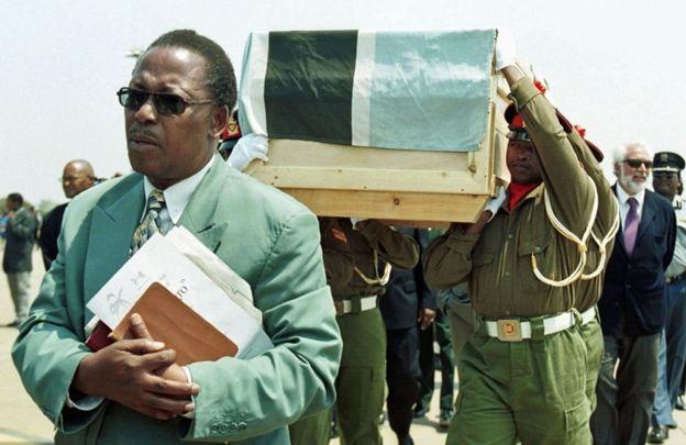 Líderes religiosos acompanham o caixão de El Negro, carregado por soldados de Botswana