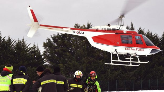A red rescue helicopter is seen landing next to workers in high-vis snow gear