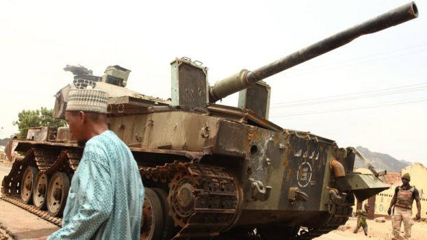 A man walks by a tank left by Boko Haram militants 10 2015.