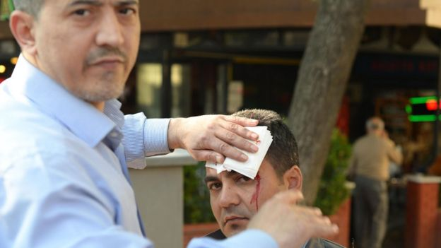 A man gives first aid to an injured man following a bombing, in Bursa, northwestern Turkey, on April 27, 2016