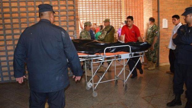 Policías trasladan el cuerpo de un miliar asesinado.