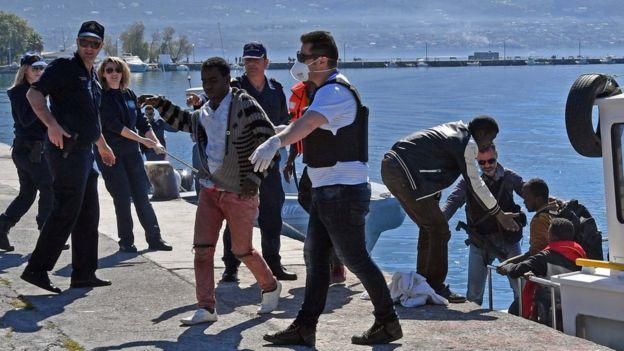Coast guard members help migrants to disembark at the port of Kalamata in South Peloponnese, Greece, 17 April 2016