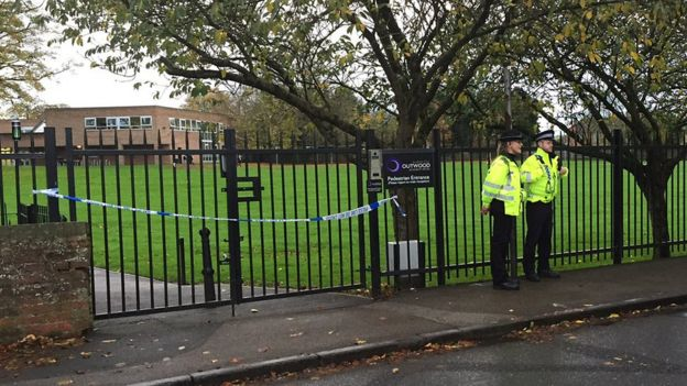Two police officers standing outside school gates