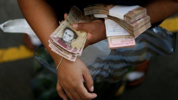Man holding piles of Venezuelan banknotes