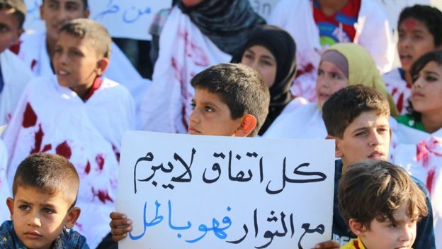 A boy carries a placard during a demonstration against the Syrian government, calling for aid to reach Aleppo, near the Castello Road (14 September 2016). The placard reads in Arabic: