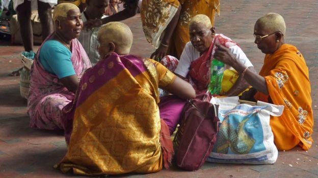 Mujeres reunidas después de que les han rasurado la cabeza en una ceremonia hindú en India.
