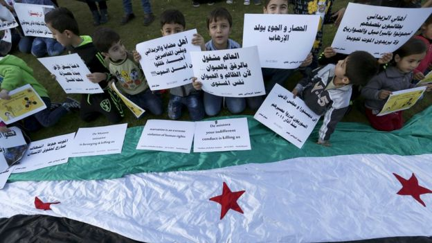 Syrian children carry placards as they call for the lifting of the siege off Madaya in Syria, in front of the offices of the UN headquarters in Beirut, Lebanon (26 December 2015)