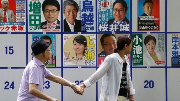 People walk past election posters in Tokyo.