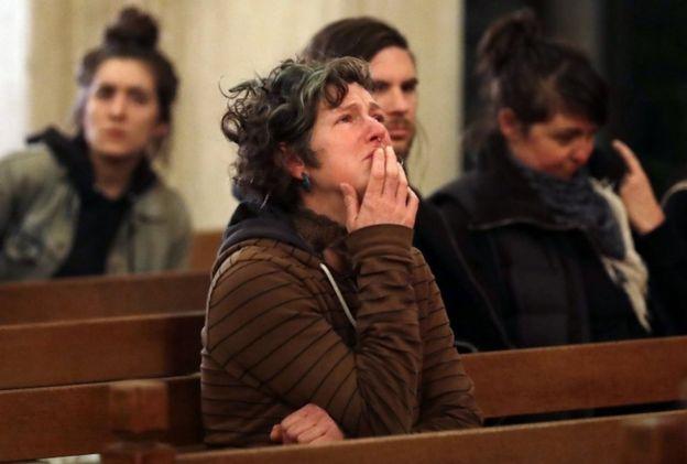 Una mujer llamada Genevieve Griseau con lágrimas en los ojos durante la ceremonia en una capilla de Oakland para recordar a las víctimas del incendio.