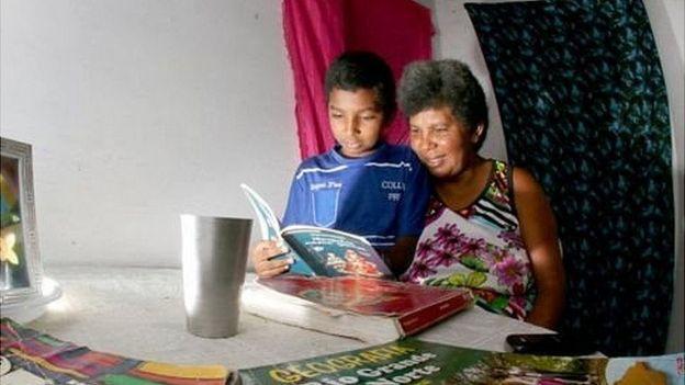 Sandra y Damiao leen un libro juntos.