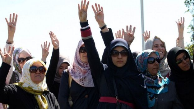Turkish demonstrators raise their hands during a protest organised by pro-Islamic groups outside the Middle East Technical University in Ankara (07 September 2013)