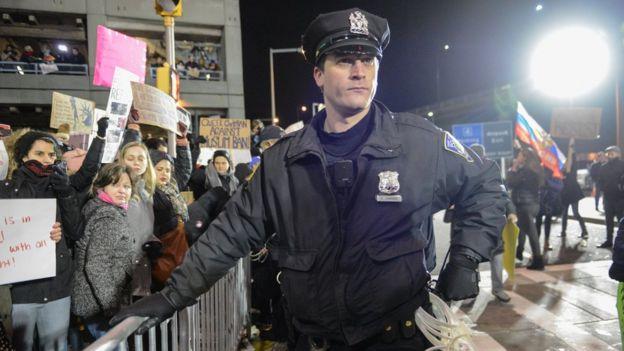 Policial na barreira contra manifestantes no aeroporto JFK, em Nova York