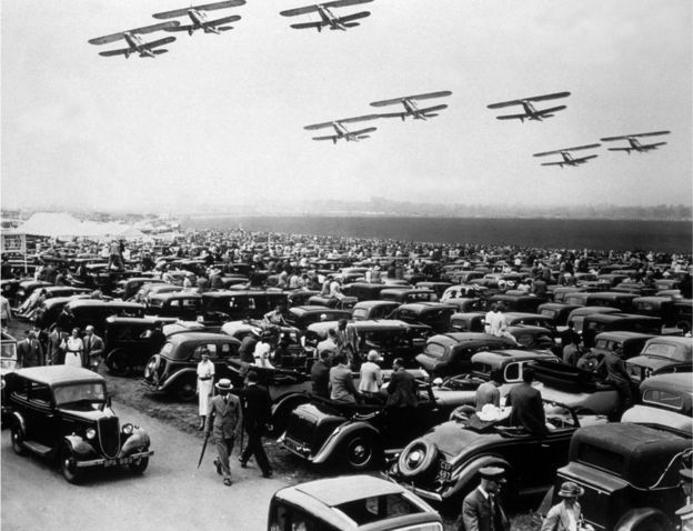 RAF aircraft flying over the packed car park, during the air display at Hendon, June 1936